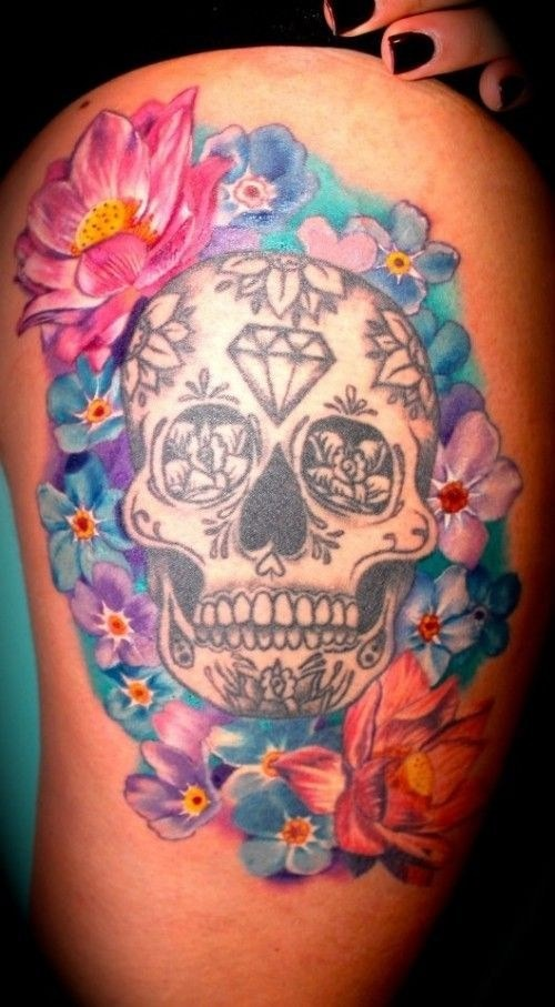 Black ink big skull tattoo on side with various multicolored flowers