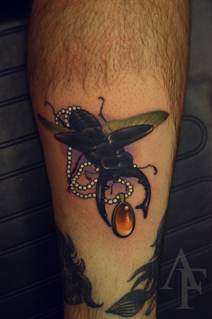 Tatuaggio realistico 3D sulla gamba l&quotinsetto con medaglione