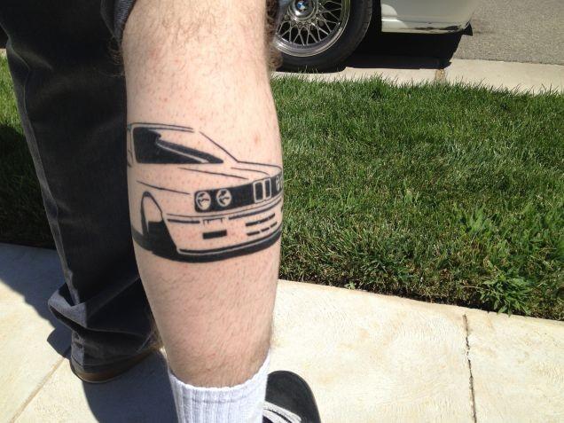 Black ink car tattoo on leg