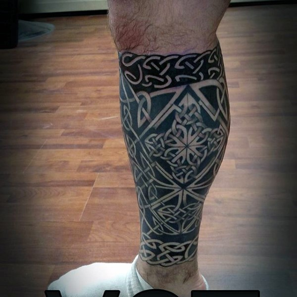 Black ink Celtic style leg tattoo of various knots