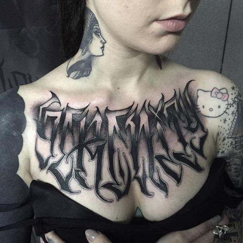 Black ink chest tattoo of mystical ambigram