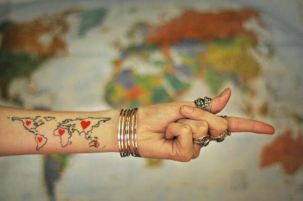Black ink contour world map with tiny red hearts tattoo on forearm zone