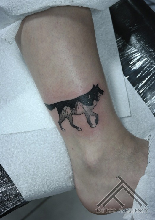 Black ink detailed leg tattoo of wolf stylized with night sky and mountains
