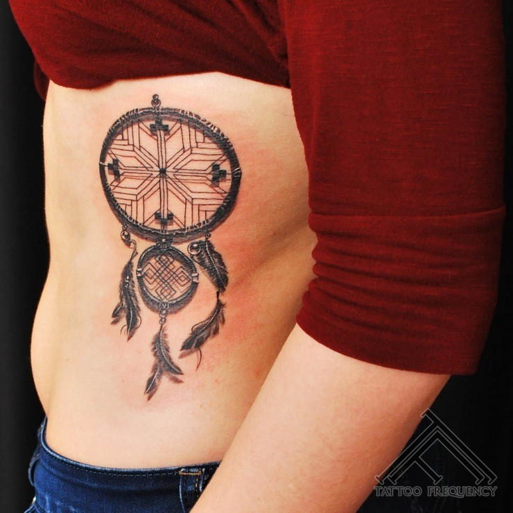 Black ink detailed side tattoo of cool dram catcher