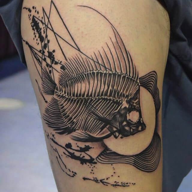 Black ink detailed thigh tattoo of big fish skeleton