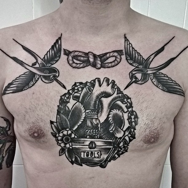 Black ink engraving style chest tattoo of flying birds with knot and human heart
