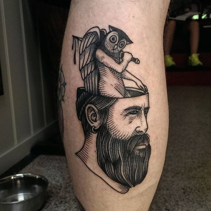 Black ink engraving style mystical man head with demonic owl tattoo on leg leg muscle