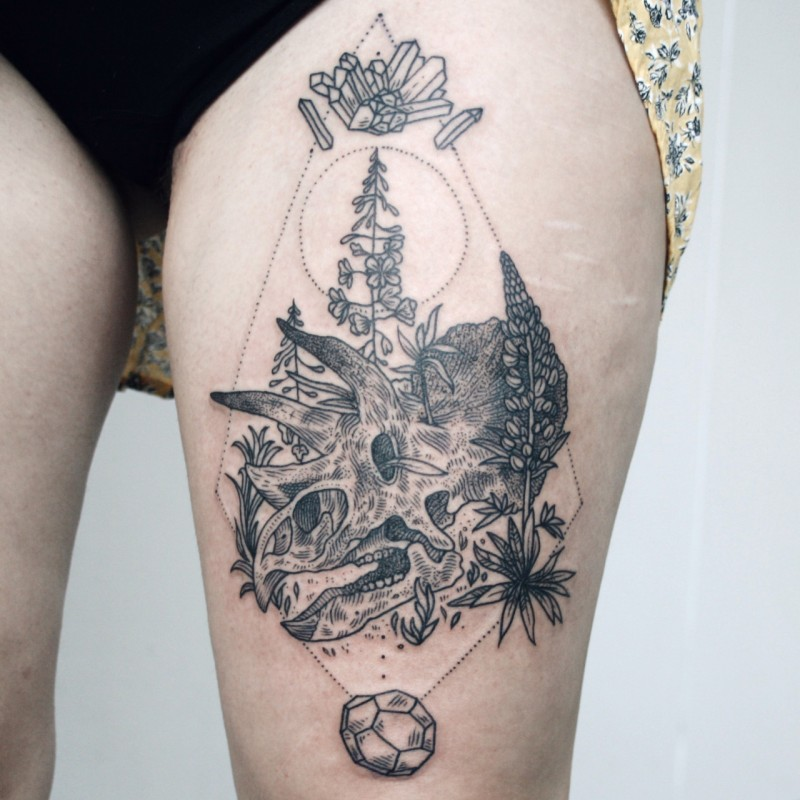 Black ink engraving style thigh tattoo of dinosaur skull and plants