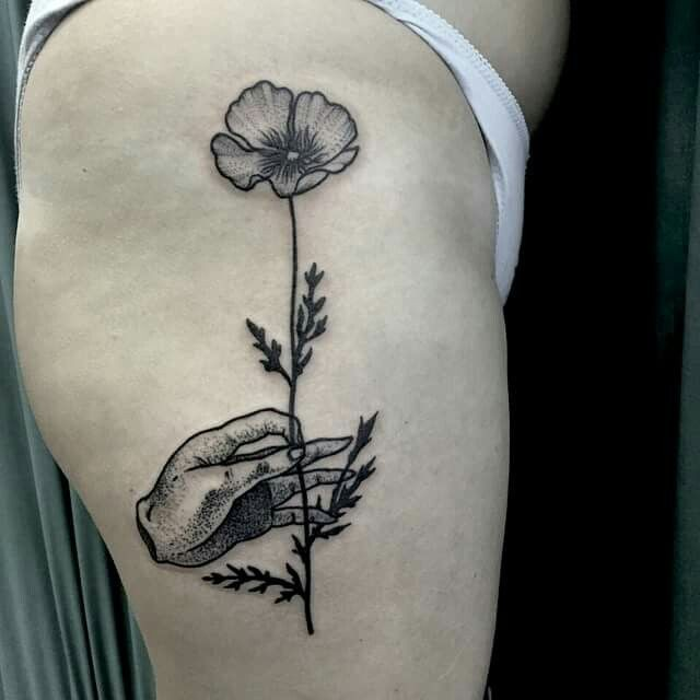 Black ink engraving style thigh tattoo of human hand holding flower