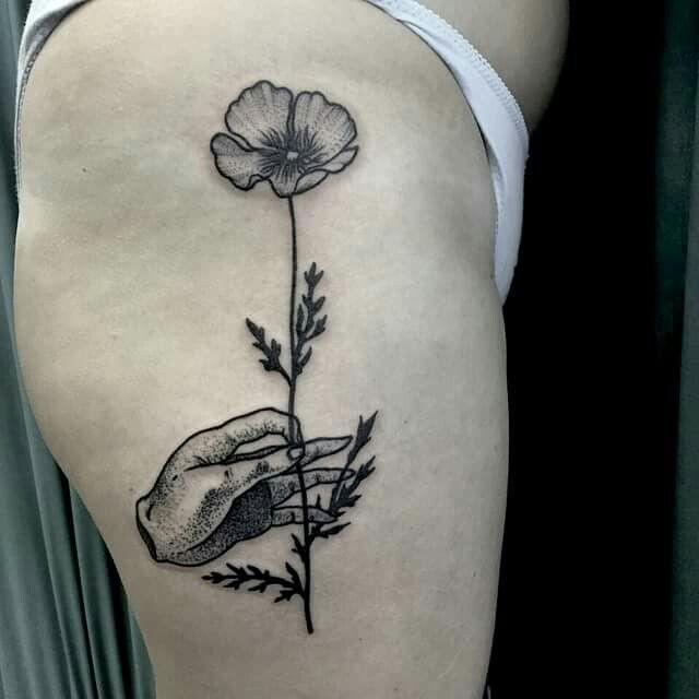 Hand holding flower tattoo