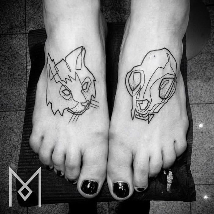 Black ink feet tattoo of cat skull and cat head