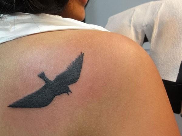 inchiostro nero uccello volante tatuaggio sulla scapola