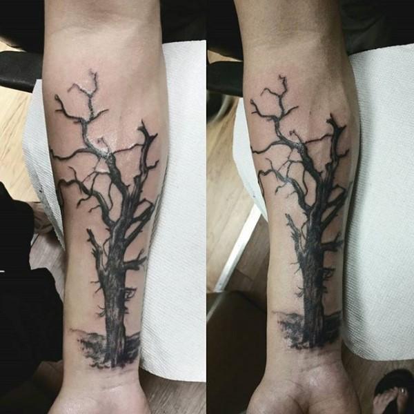 Black ink forearm tattoo of dark tree
