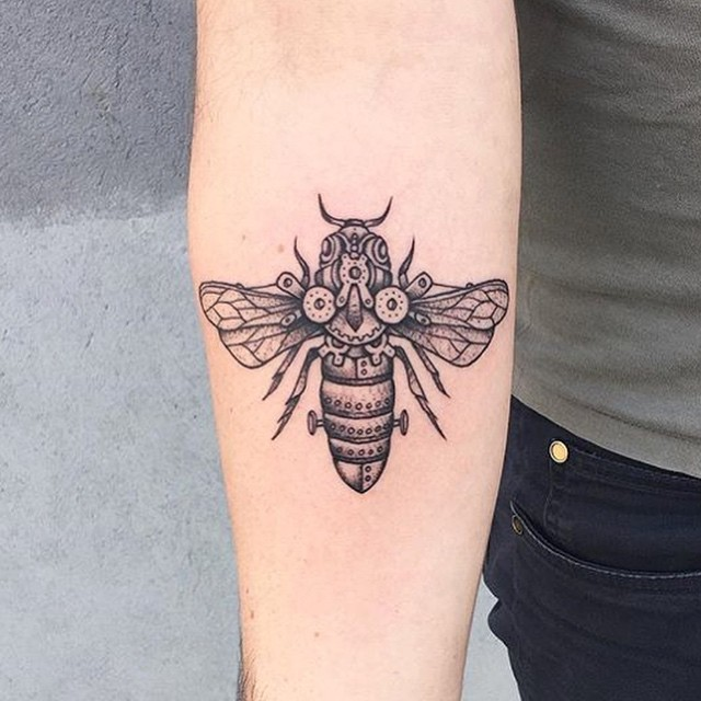 Black ink forearm tattoo of mechanical bee