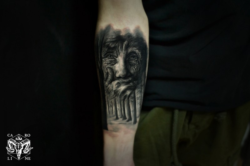 Black ink forearm tattoo of old woman and dark forest