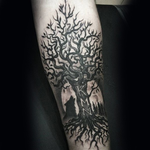 Black ink forearm tattoo of tree with lettering