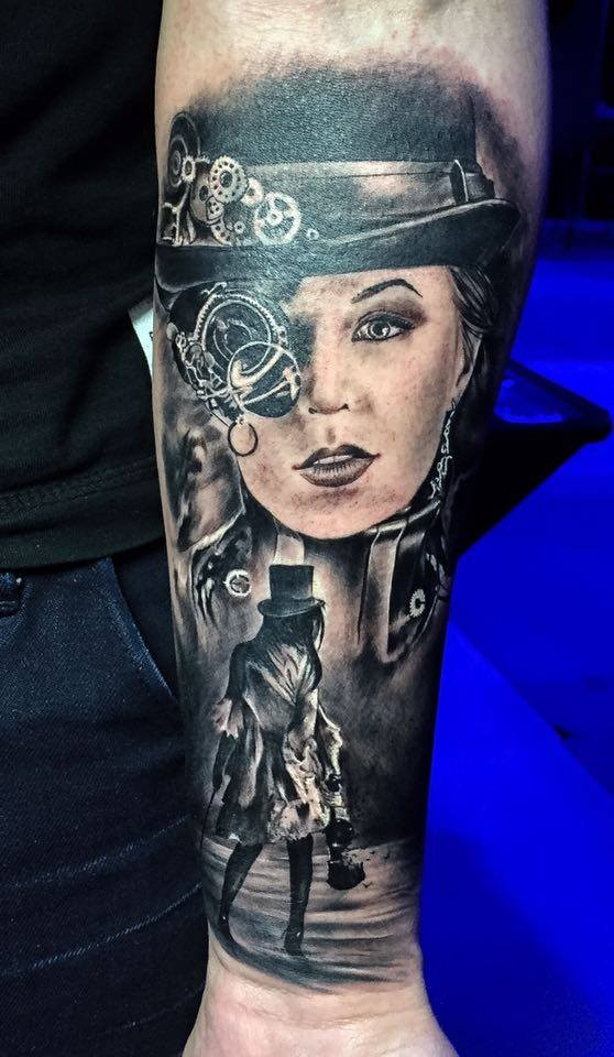 Black ink forearm tattoo of woman with mechanical eye