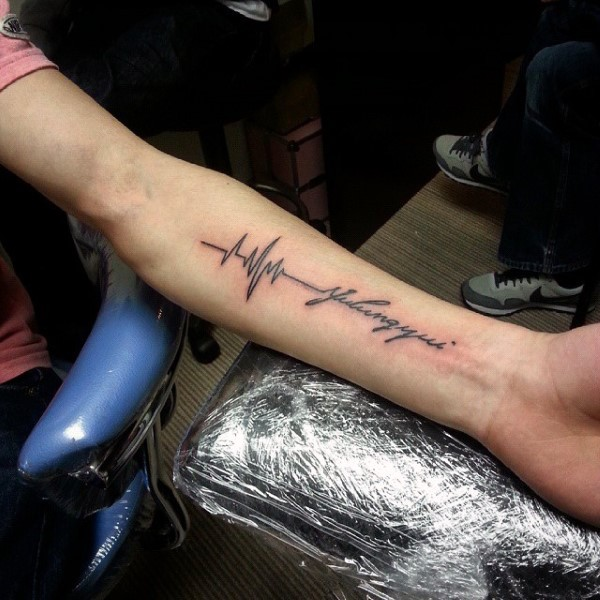 Black ink heart rhythm tattoo with lettering on arm