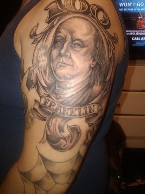 Black ink homemade shoulder tattoo of Benjamin Franklin portrait with lettering