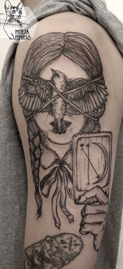 Black ink illustrative style shoulder tattoo of woman face with tied bird and card
