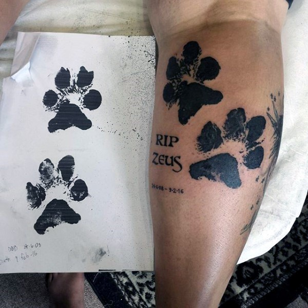 Black ink impressive looking black ink leg tattoo of animal paw prints with lettering