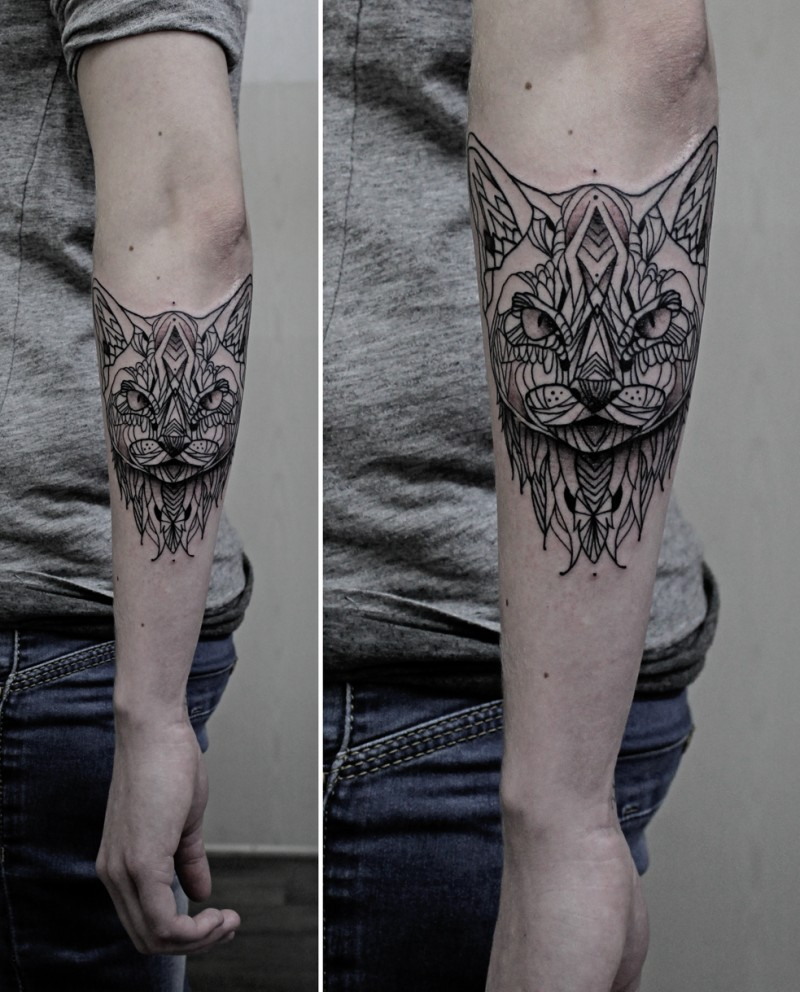 Black ink interesting looking mystical cat tattoo on forearm