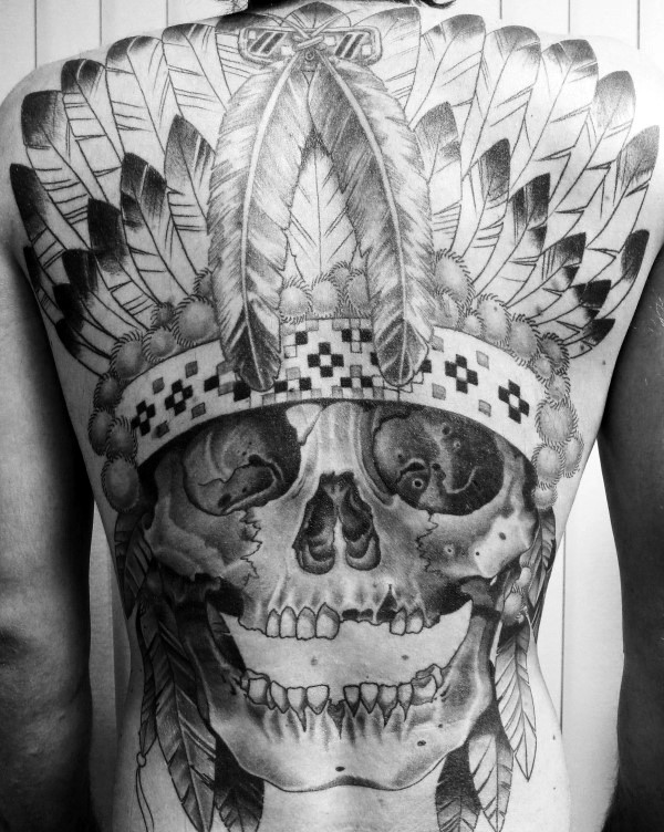 Black ink large whole back tattoo of detailed Indian skull with feather helmet