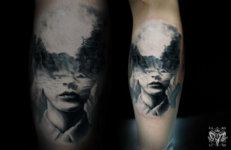 Black ink leg tattoo of human face stylized with mountain forest