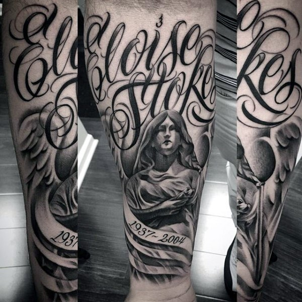 Black ink memorial forearm tattoo of angel statue with lettering and date