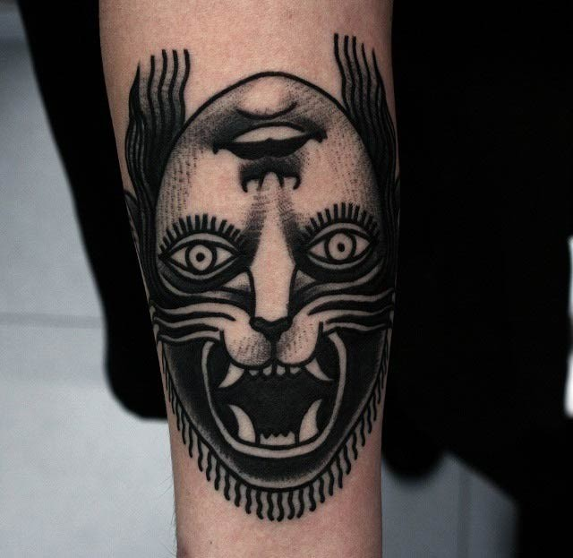 Black ink mystical looking arm tattoo of half human half lion face