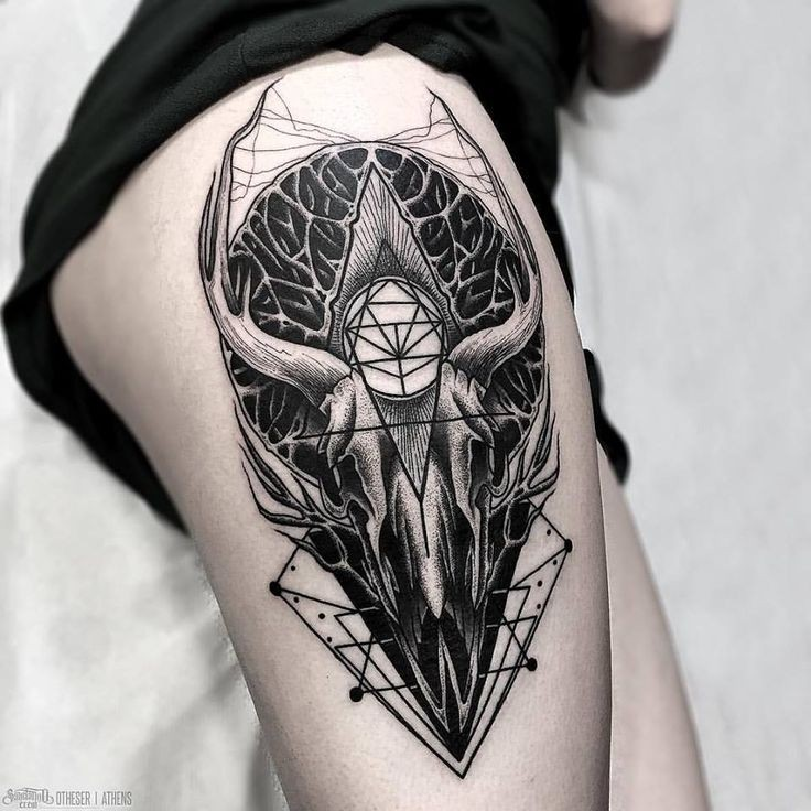 Black ink mystical thigh tattoo of large animal skull with mysterious ornaments