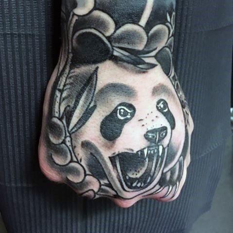 Black ink original looking hand tattoo of panda bear with leaves