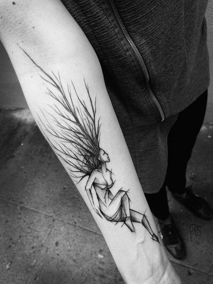 Black ink painted by Inez Janiak forearm tattoo of strange woman sketch