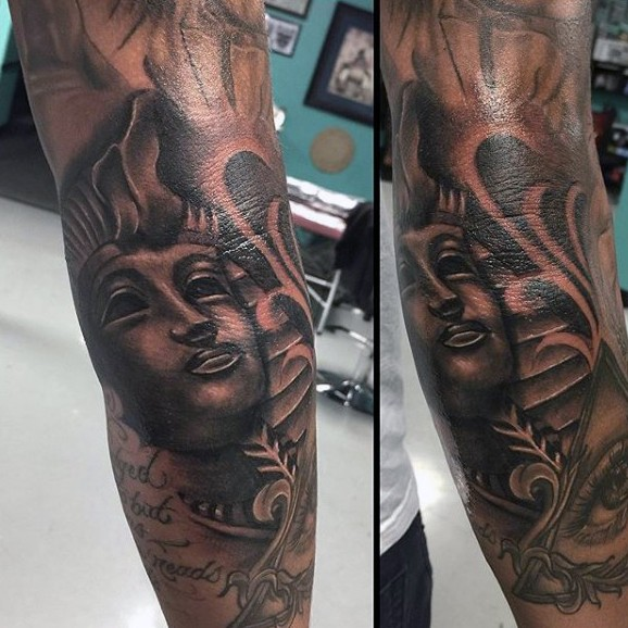 Black ink painted Egypt pharaoh statue tattoo on forearm with lettering