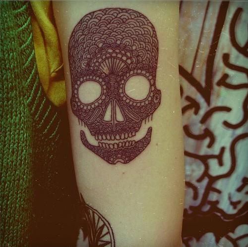 Tatuaggio nero bianco sul braccio il teschio stilizzato