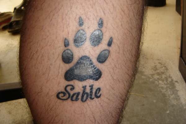 Tatuaje en la pierna, huella negra del perro, sable