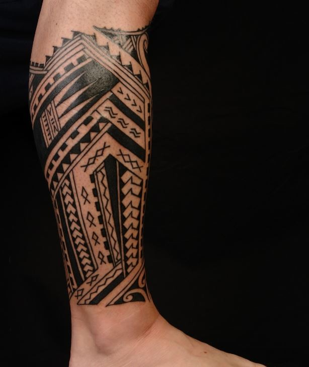 Black ink polynesian tattoo on leg