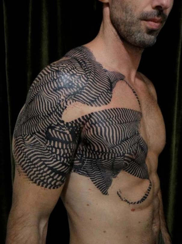 Black ink shoulder and chest tattoo of various ornaments