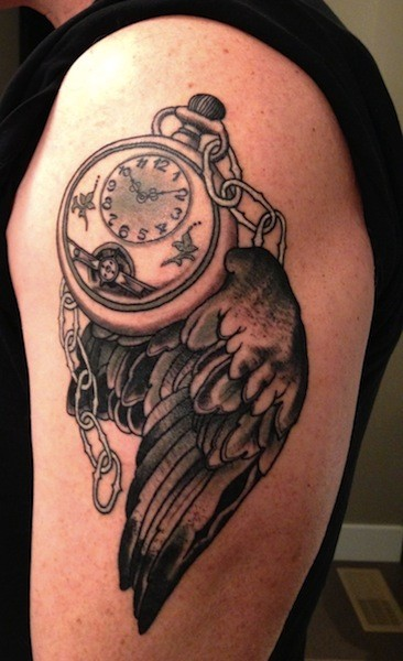 Black ink shoulder tattoo of bird wing with chained clock