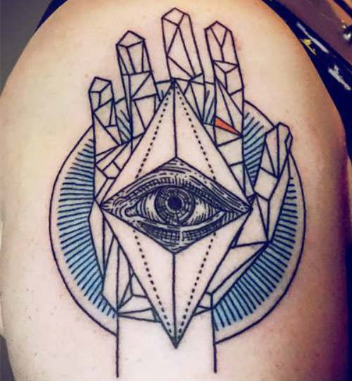 Black ink shoulder tattoo of human hand with eye tattoo in geometrical style
