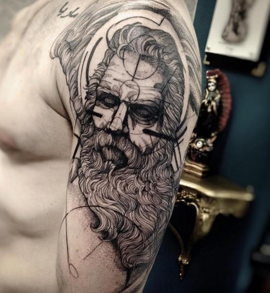 Black ink shoulder tattoo of mystical man with beard
