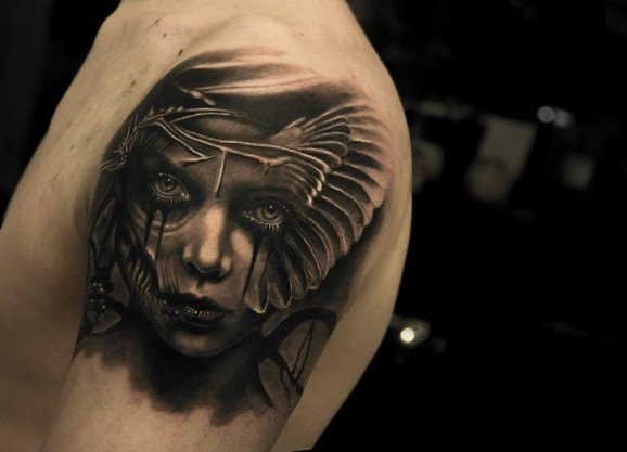 Black ink shoulder tattoo of woman with mask