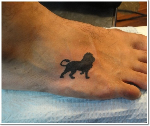 Black ink silhouette lion tattoo on foot