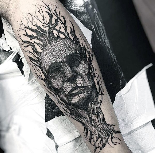 Black ink strange looking engraving style tattoo of old tree with mans face