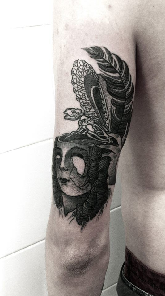 Black ink surrealism style arm tattoo of woman face with lizard skeleton and feather