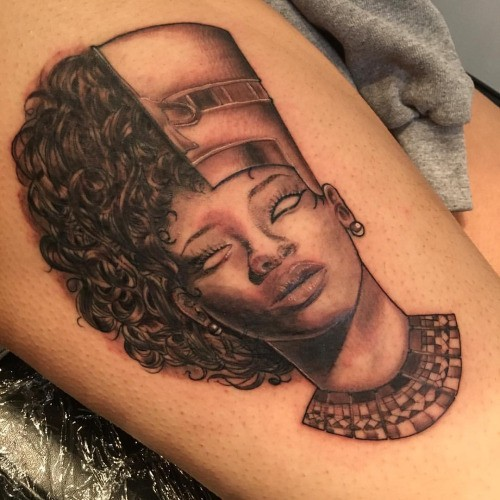 Black ink thigh tattoo of half modern half Egypt woman