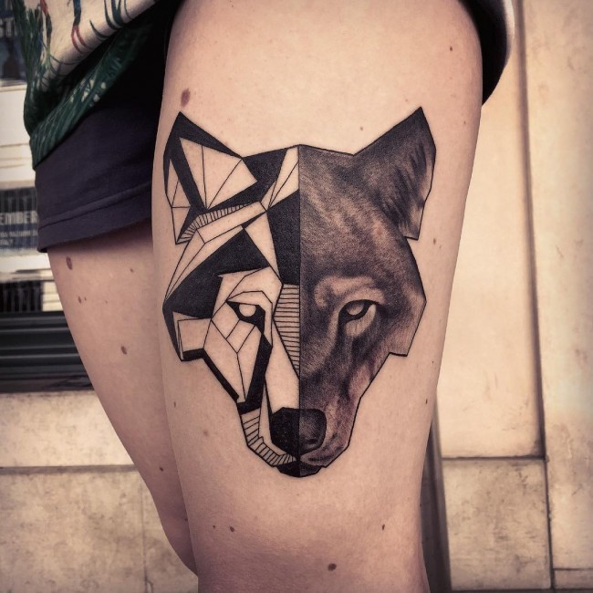 Black ink thigh tattoo of half real half tribal wolf head