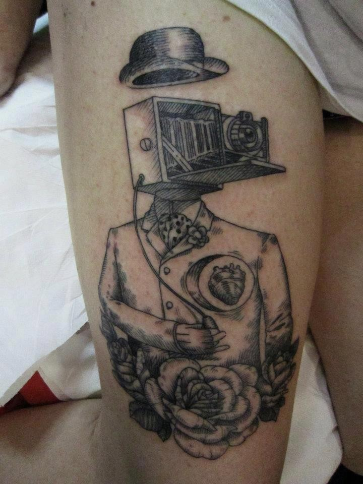 Black ink thigh tattoo of human body with old camera and hat