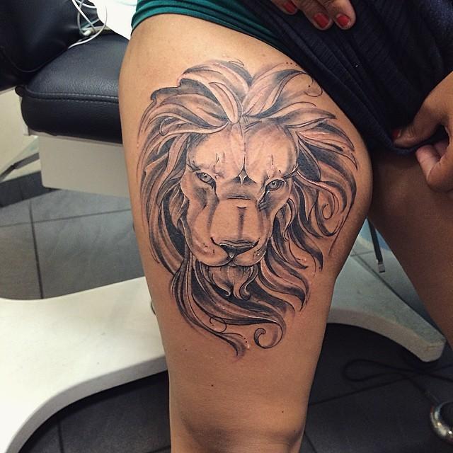 Black ink thigh tattoo of realistic lion head