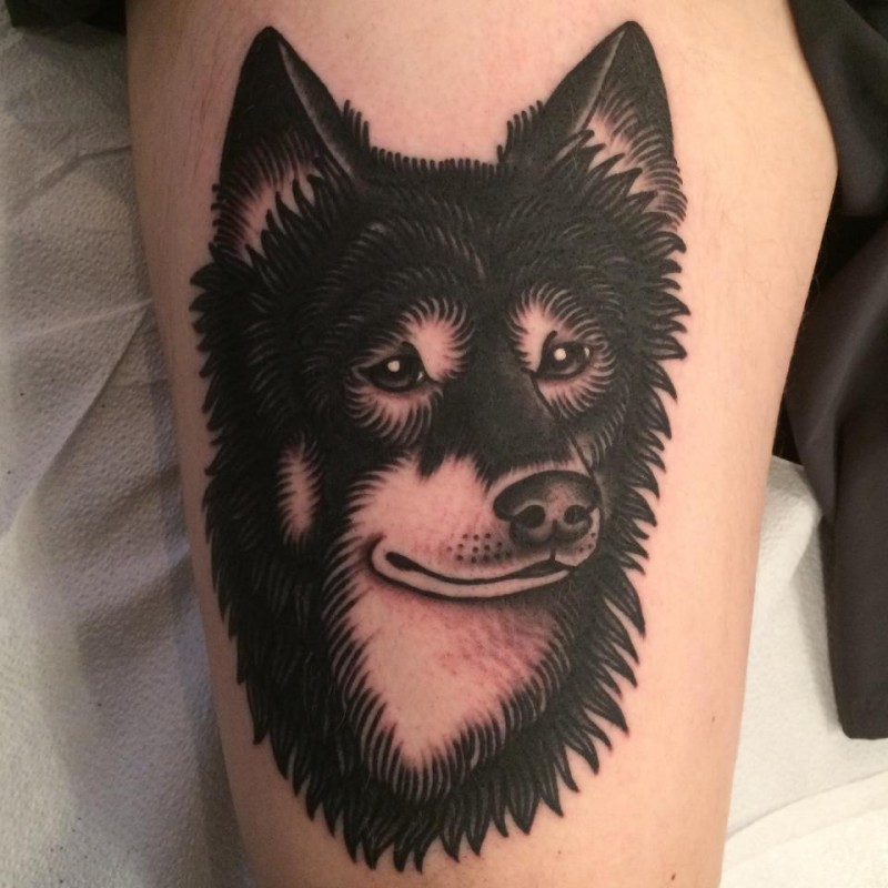 Black ink thigh tattoo of sad wolf head